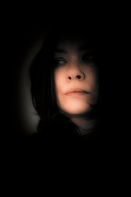Portrait of woman hiding in the dark - p1047m987402 by Sally Mundy