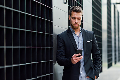Young businessman looking at his smartphone - p300m1587144 von Javier Sánchez Mingorance