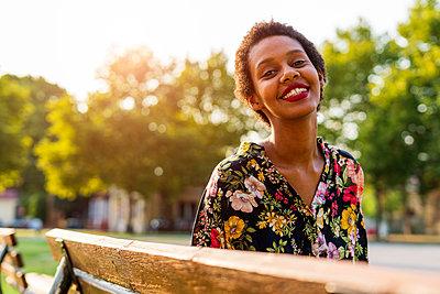 Portrait of smiling young woman on bench in a park - p300m2041869 von Giorgio Fochesato