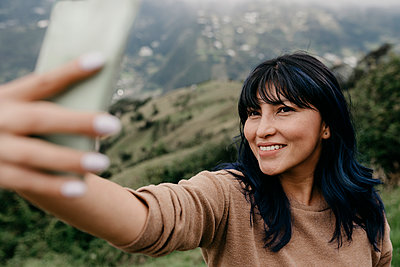 Smiling woman with bangs taking selfie through smart phone during vacations - p300m2274474 by MORNINGVIEW AGENCY