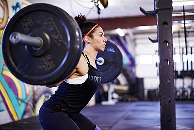 A female athlete trains in a crossfit gym.  - p343m1184143 by Josh Campbell