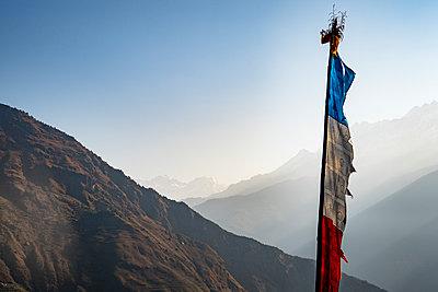 Prayer flag against sky, Goljung, Rasuwa, Nepal - p343m2032544 by Sarah Ann Loreth