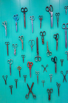 Collection of scissors hanging on green wall - p429m2058441 by Seb Oliver