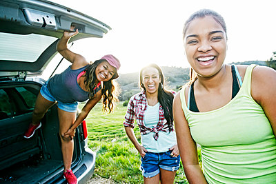 Mixed Race mother and daughters at hatch of car laughing - p555m1305270 by Peathegee Inc