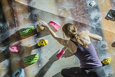 Athlete climbing rock wall in gym - p555m1411977 by John Fedele