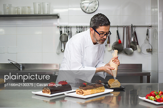 Chef decorating cakes with pastry bag in hands - p1166m2130375 by Cavan Images