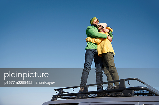 Happy couple on a SUV rooftop in their road trip - p1577m2289482 by zhenikeyev