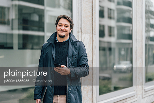 Portrait of smiling young man with cell phone in the city - p300m1586956 von Gustafsson