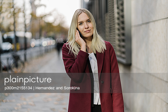 Blond businesswoman using smartphone in the background modern building - p300m2155134 by Hernandez and Sorokina