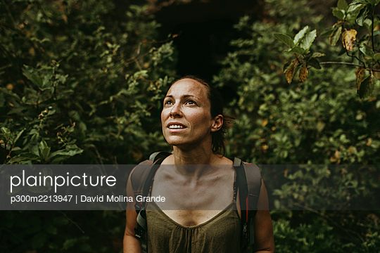 Thoughtful woman explorer standing in forest - p300m2213947 by David Molina Grande