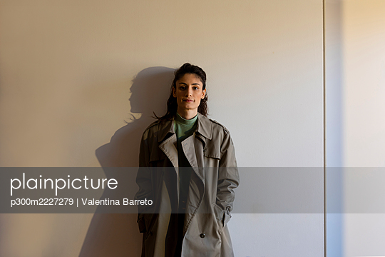 Female model wearing jacket with hands in pockets standing against wall - p300m2227279 by Valentina Barreto