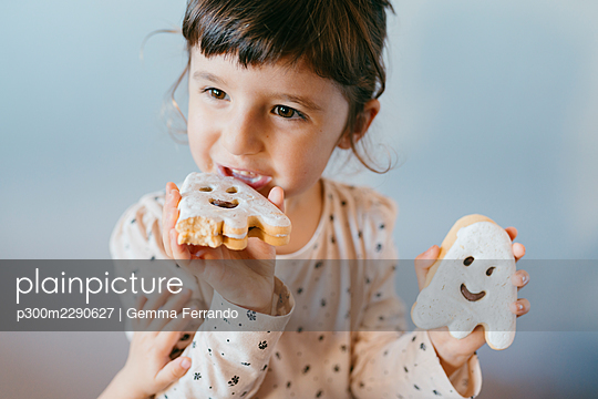 Little girl eating homemade halloween ghost cookies - p300m2290627 by Gemma Ferrando