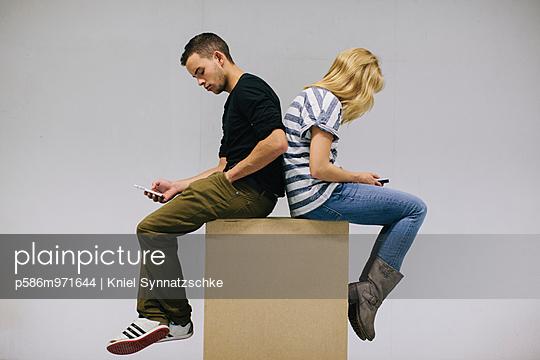 Junges Paar sitzt Rücken an Rücken - p586m971644 von Kniel Synnatzschke