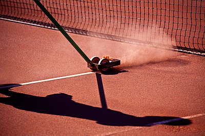 View of shadow cleaning the border line at a tennis clay court - p1025m788491f by Mujo Korach