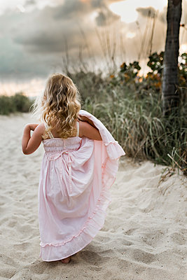 Rear view of girl holding dress while standing on sand at beach - p1166m1473792 by Cavan Images