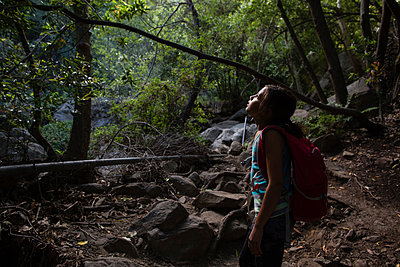 Side view of girl exploring while standing in forest - p1166m1489685 by Cavan Images