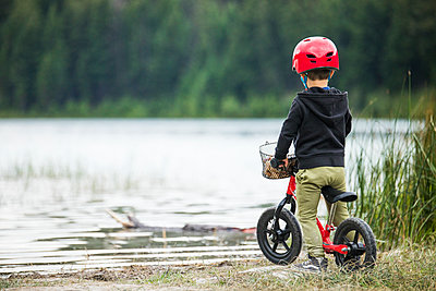 Rear view of young boy on balance bike looking out at lake. - p1166m2147369 by Cavan Images