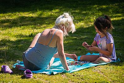 Ältere Frau spielt mit ihrer Enkelin im Garten ein Spiel - p1418m2008128 von Jan Håkan Dahlström