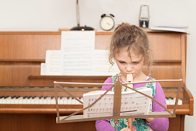 Girl at music stand playing recorder - p300m1019451f by Ophelia photography