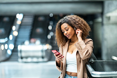 Young woman with cell phone and earbuds at subway station - p300m2167642 by William Perugini