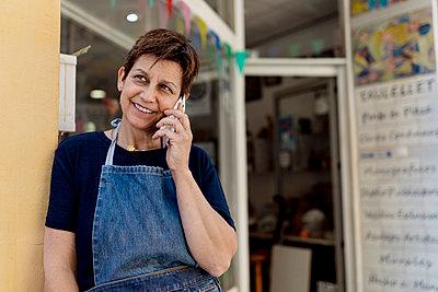 Mature store owner talking on mobile phone standing by door of workshop - p300m2240687 by Ezequiel Giménez