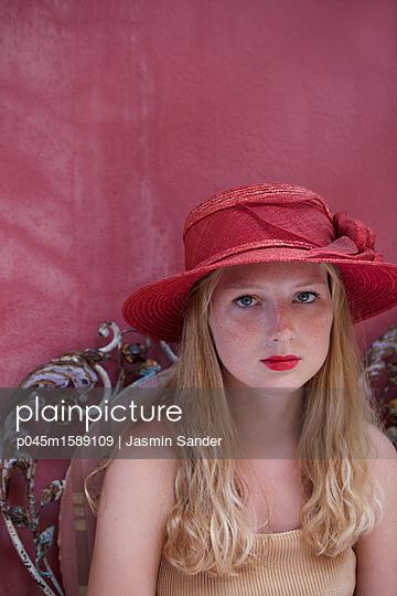 Frau mit rotem Hut vor roter Wand - p045m1589109 von Jasmin Sander