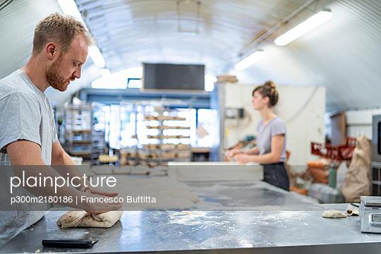 Man and woman preparing bread in bakery - p300m2180186 by Francesco Buttitta