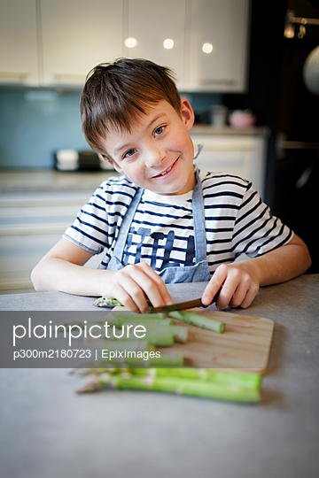 Portrait of smiling little boy cutting green asparagus in the kitchen - p300m2180723 by Epiximages