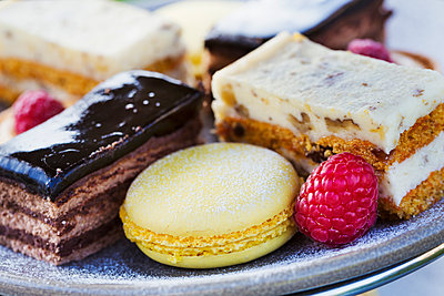 Close up of a selection of cakes, a cream slice and a macaroon and a raspberry on a plate, traditional afternoon tea.  - p1100m1450819 by Mint Images