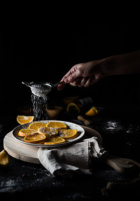 oranges on a plate with a hand sprinkling sugar - p1166m2088594 by Cavan Images