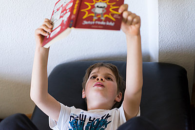 Boy reading book at home, stay at home due to Covid-19 - p1498m2183733 by Nina King