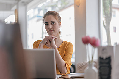 Young woman sitting in coworking space,using laptop - p300m2024047 von Joseffson
