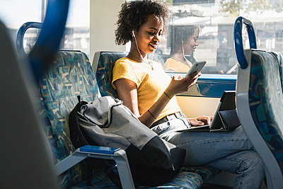 Young woman with earphones using smartphone and tablet on a train - p300m2155856 by Uwe Umstätter