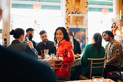 Portrait of smiling young woman sitting amidst multi-ethnic friends during brunch party in restaurant - p426m2046322 by Maskot