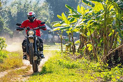 Biker exploring countryside, Nan, Thailand - p429m2078583 by Henn Photography