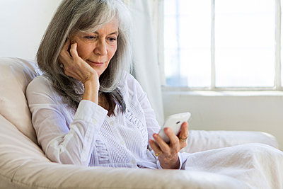 Senior woman looking at smartphone - p924m895708f by Luc-Richard Photography