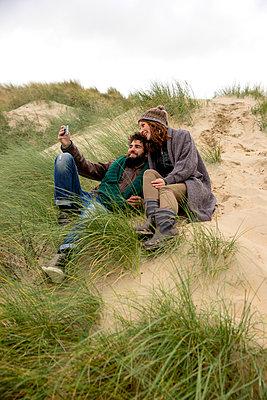 Paar macht Selfie in den Dünen - p1212m1185646 von harry + lidy