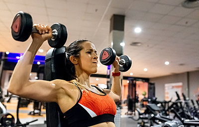 Woman lifting dumbbells in gym - p300m1449921 by Marco Govel