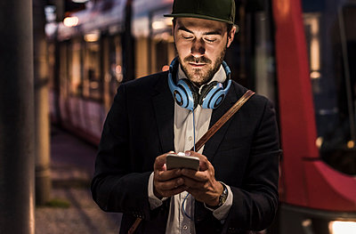Young man in the city checking cell phone in the evening - p300m1460272 by Uwe Umstätter