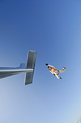 Mid adult woman jumping out of airplane - p31226171 by Hans Berggren