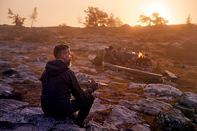 Hiker relaxing with coffee on rocky field, Sarkitunturi, Lapland, Finland - p429m1188085 by Aleksi Koskinen