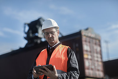 Engineer using digital tablet at port - p429m2164619 by Sigrid Gombert