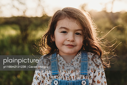 Portrait of young school-aged girl with sunlight in her hair - p1166m2131238 by Cavan Images