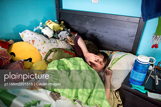 Boy in bed rubs eyes while waking up with cat sharing his pillow - p1166m2201515 by Cavan Images