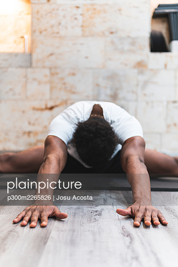 Flexible man stretching while practicing Pilates against wall at health club - p300m2265826 by Josu Acosta