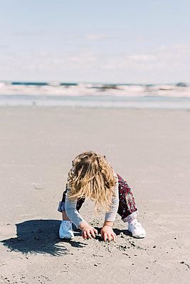Little girl digging with her bare hands at a beach in New England - p1166m2212923 by Cavan Images