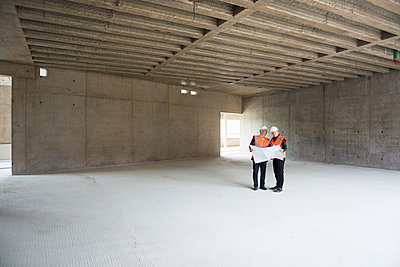 Two men with plan wearing safety vests talking in building under construction - p300m1460219 by Daniel Ingold