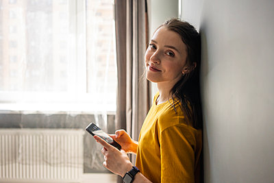Smiling woman holding mobile phone while leaning on wall - p300m2282574 by Vasily Pindyurin