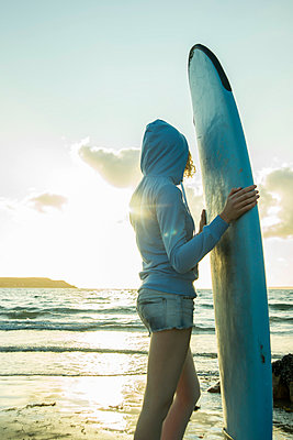 Teenage girl standing on the beach with her surfboard looking at horizon - p300m965192f by Uwe Umstätter