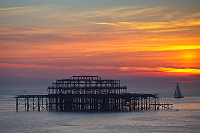 UK, England, Sussex, Brighton, Boat sailing past burn out remains of Brighton west pier at sunset - p651m860982 by Jane Sweeney